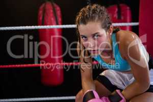 Portrait of young female boxer sitting at corner
