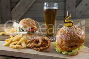 Hamburger, french fries and onion ring with glass of beer