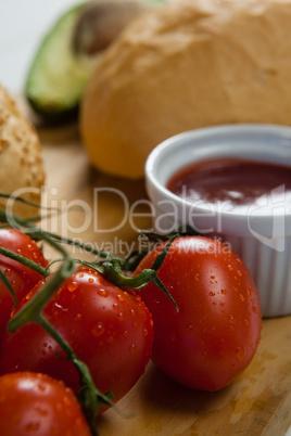 Buns, cherry tomato, sauce on chopping board