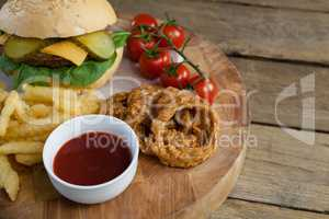 Hamburger, onion ring, tomato sauce, cherry tomato and french fries on chopping board