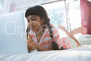 Tilt shot of girl typing laptop on bed