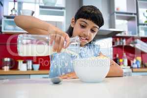 Girl pouring milk in breakfast bowl