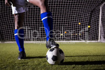 Low section of male soccer player standing with ball on field