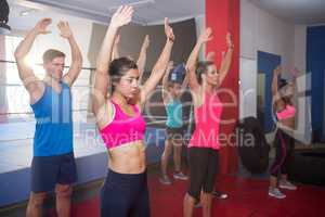 Young athletes exercising with arms raised
