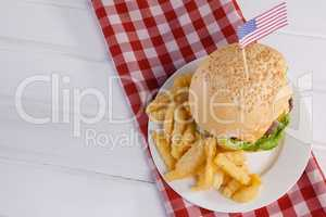 Burger decorated with american flag and french fries in plate