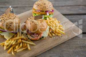 High angle view of burgers with french fries served on cutting board