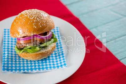 Hamburger served on napkin in plate