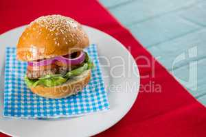 Hamburger served on napkin in plate