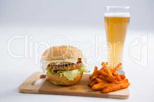Burger with spicy French fries by beer glass