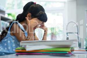 Side view of exhausted girl sitting by books in kitchen