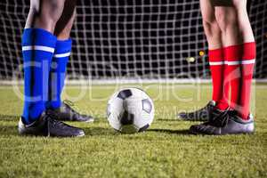 Low section of male players standing by soccer ball against goal post