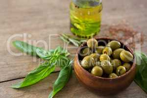 Marinated green olives in bowl and oil container with green leaf on table