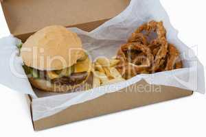 Hamburger, onion ring and french fries in a take away container on table