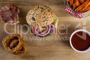 Hamburger, french fries, onion ring and tomato sauce on chopping board