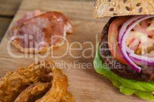 Hamburger and onion ring on chopping board