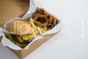Close up of burger with onion rings and French fries in box