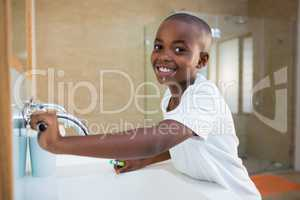 Side view portrait of smiling boy with toothbrush looking at mirror