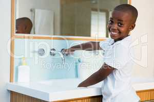 Side view portrait of smiling boy washing hands in sink