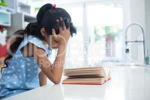 Girl with hand in hair reading novel in kitchen