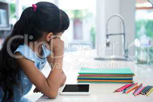 Girl looking away while sitting with tablet and colored pencils