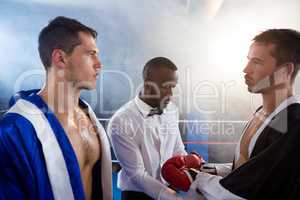 Referee checking gloves of male boxer