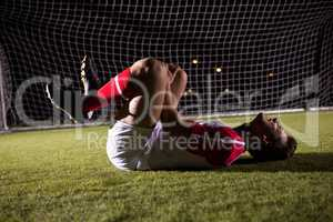 Side view of young male soccer player suffering from knee pain