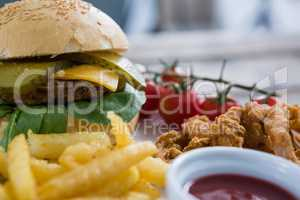 Close up of burger and fries with onion rings by sauce