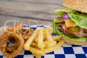 Close up of burger and onion rings with french fries