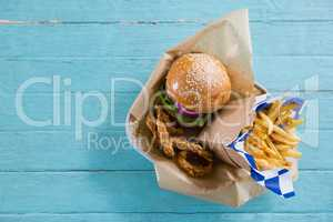 Overhead view of burger with french fries and onion rings in container