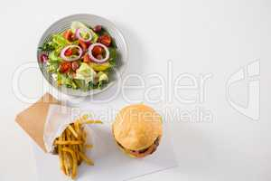 High angle view of salad with burger and French fries