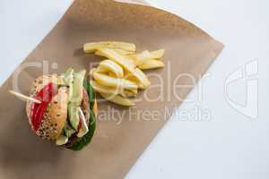 Overhead view of burger with French fries on paper