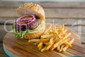 French fries with hamburger on cutting board