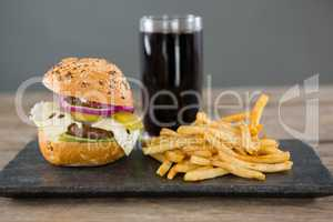 Cheeseburger with french fries and drink on slate