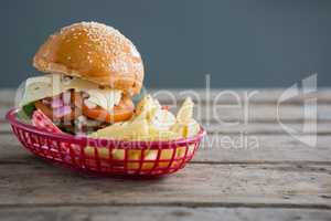 Cheeseburger and French fries in basket