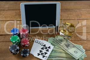 High angle view of digital tablet and whisky with currency on table during poker game