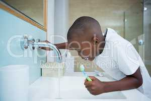 Side view of boy spitting while holding brush in sink