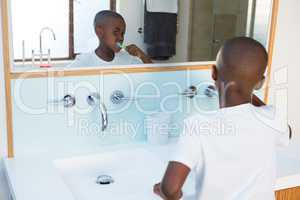 Boy brushing teeth looking at mirror reflection