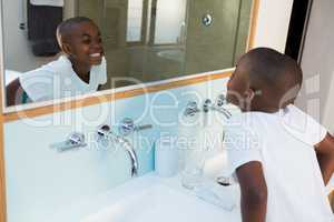 High angle view of boy clenching teeth while looking at mirror