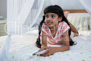 Girl holding remote control while lying on bed
