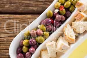 Marinated olives, bread pieces and olive oil in platter