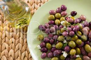 Marinated olives with olive oil on bamboo mat