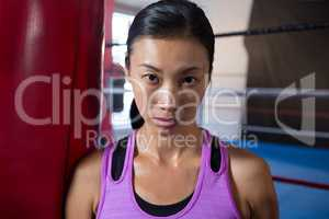 Close-up portrait of confident young female athlete against boxing ring