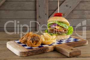 Hamburger, onion ring and french fries on chopping board