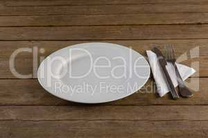 White plate with cutlery and napkin on table