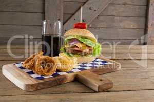 Hamburger, onion ring and french fries with cold drink on chopping board