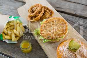 High angle view of burger with onion rings and french fries on cutting board