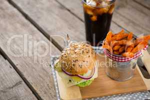 French fries in container by burger on cutting board with drink