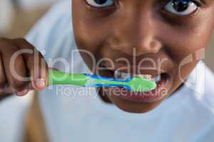 Mid section of boy brushing teeth