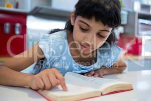 Close-up of girl pointing while reading novel in kitchen