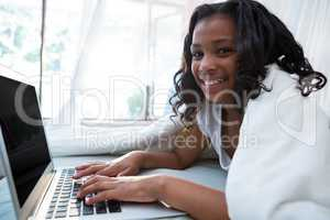 Portrait of girl using laptop on bed